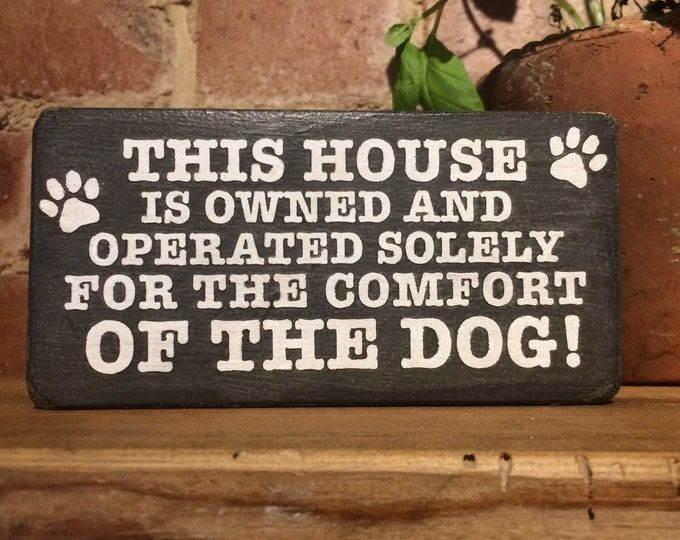 This house is owned and operated solely for the comfort of the dog wooden block sign