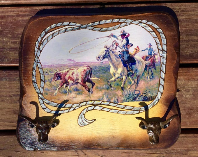 Rustic, vintage decoupaged western art print by Olaf C. Seltzer, antiqued rustic wood backplate with iron steer head hooks, rope accent