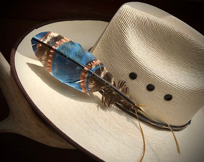 Custom mini hat feather, hand painted metallic blue with coral and copper tribal theme on a small turkey wing feather, hand tied sinew