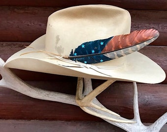 American cowboy hat feather, new retro rustic version of an old tradition, hand painted turkey wing in navy blue, turquoise stars, rust, tan