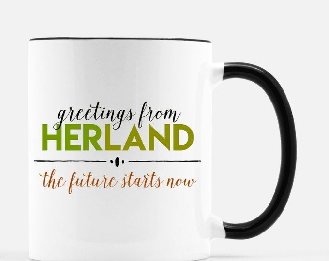 Greetings from Herland. 11 0z ceramic cup or 10 oz metal cup. Free shipping to continental US