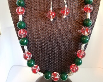 This Beaded Necklace has Clear with Red speckles, Solid Green, Clear and includes Silver Accents
