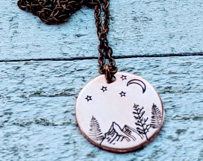 Outdoor scene copper necklace. Trees. Outdoors. Mountains. Wyoming.