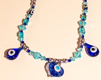 Single blue eye necklace, three blue eye glass pendants, separated by blue crystals and smaller blue eye beads