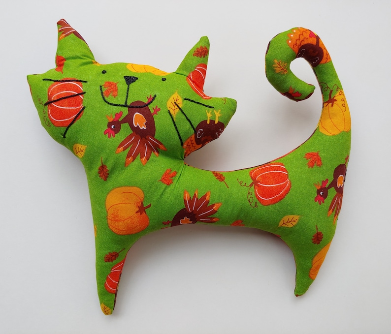 green turkeypumpkin print on front and brown autumn leaves on back Avery Stuffed Cat