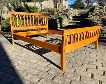 Cherry bed frame with curved, carved headboard and footboard