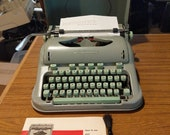 1963 Curvy Hermes 3000 portable typewriter with lid, manual, and cleaning brush