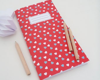 Long notebook, 11x20cm, illustrated with blue and white hearts on red background