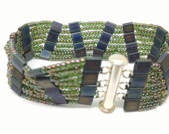 Beaded ladder bracelet. Green seed beads and matt black iris tile beads