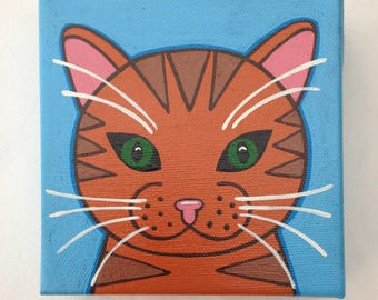 """A 5"""" square canvas hand painted with a ginger cat face"""
