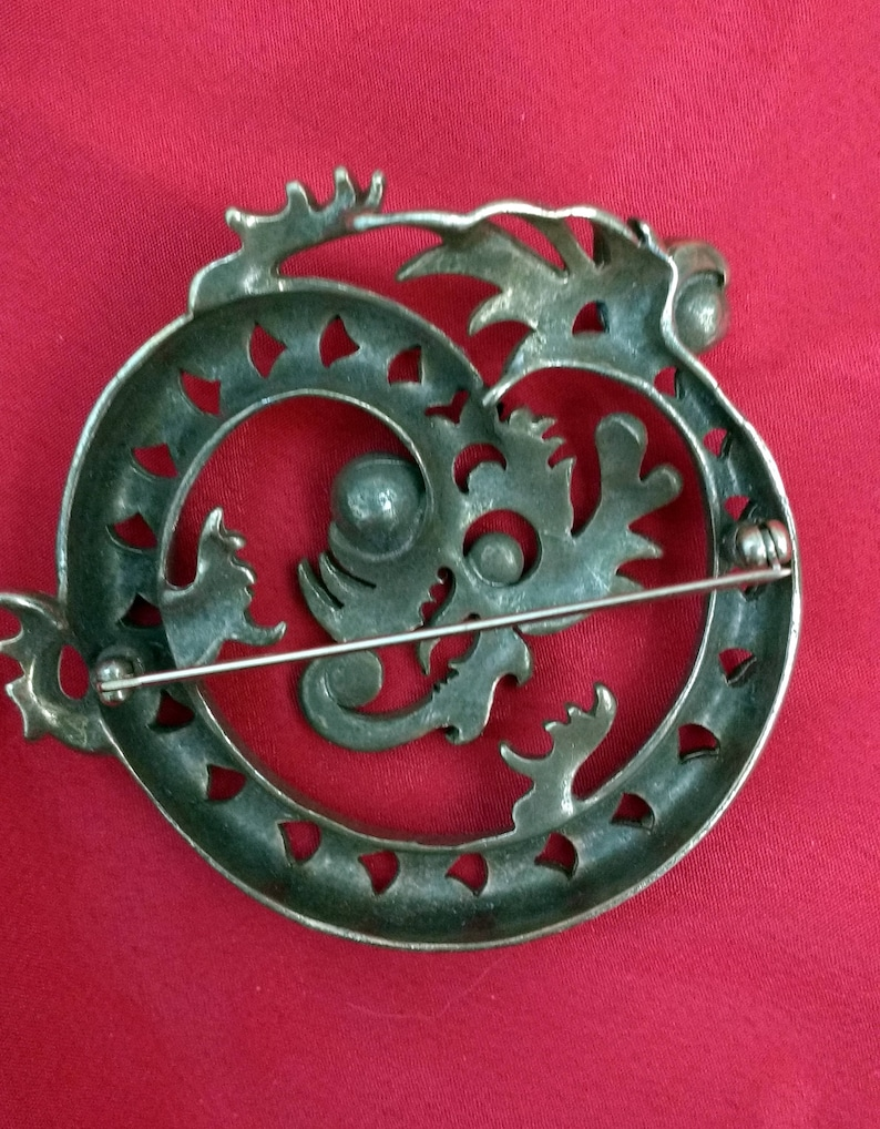stylized coiled brass dragon brooch with plastic red and white stones.