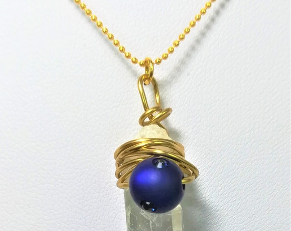 neklace with a tip of rock crystal pendant, a gold plated star, a swarovski strassed pearl dark blue and a extrafine gold plated chain