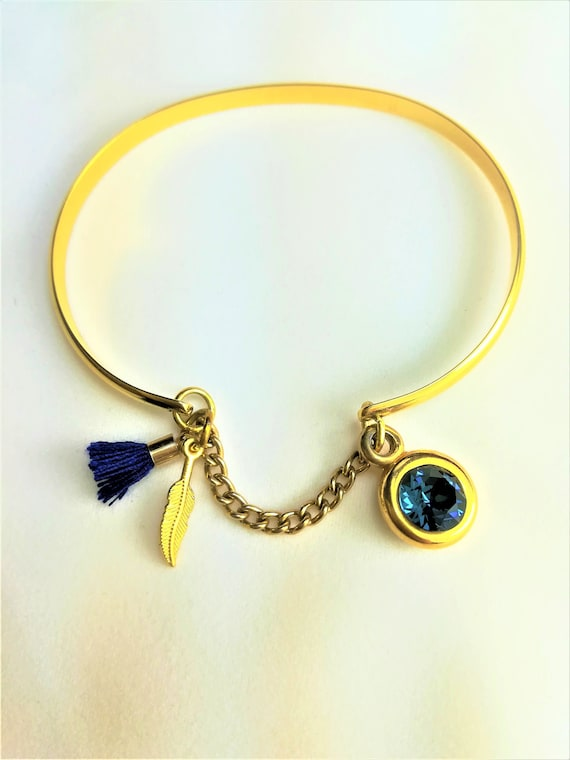golden plated bangle with a blue pompon, a swarovski faceted cabochon and a goldent plated chain