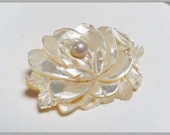 A intricate carved mother of pearl floral brooch with a pearl in the centre