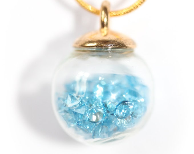 60 cm necklace/pendant with a golden chain and a 1,5 cm glass vial containing blue rhinestones