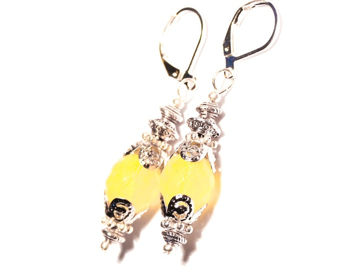 Earrings with opaque yellow faceted glass bead and silver elements