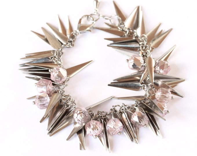 Silver bracelet with a lot of silver spikes charms and light pink glass beads