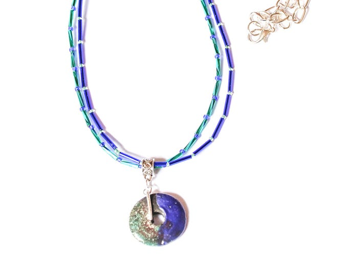 Blue necklace with small glass tubes and and ceramic disc