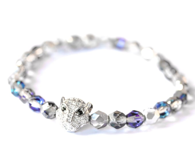 Bracelet with a silver panther head with zirconium, and silver and blue glass beads