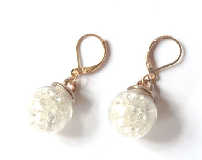 Gold leverback earrings with spherical vials containing clear rhinestones