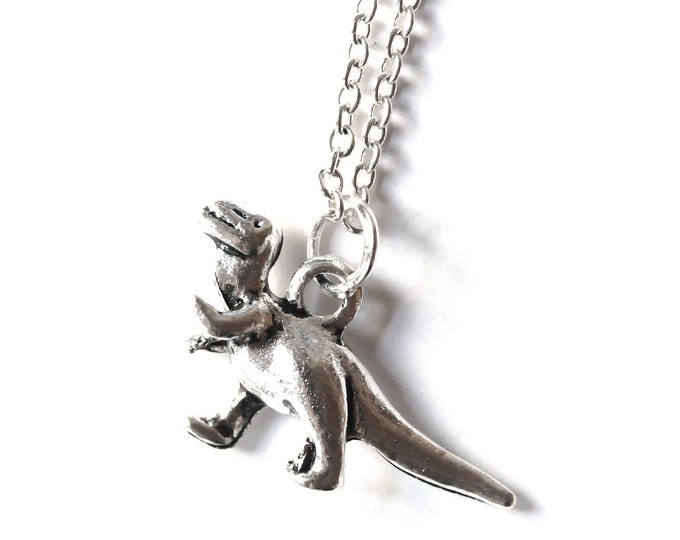 Thin silver chain necklace with a dinosaur pendant