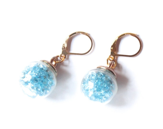 Gold leverback earrings with spherical glass vials containing blue rhinestones