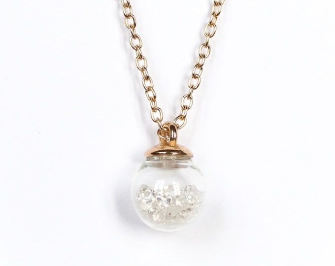 90 cm necklace/pendant with a golden chain and a 1,5 cm glass vial containing rhinestones