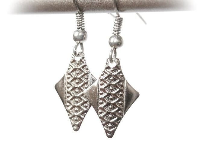 Silver earrings with arrow shaped charms showing geometric printed pattern