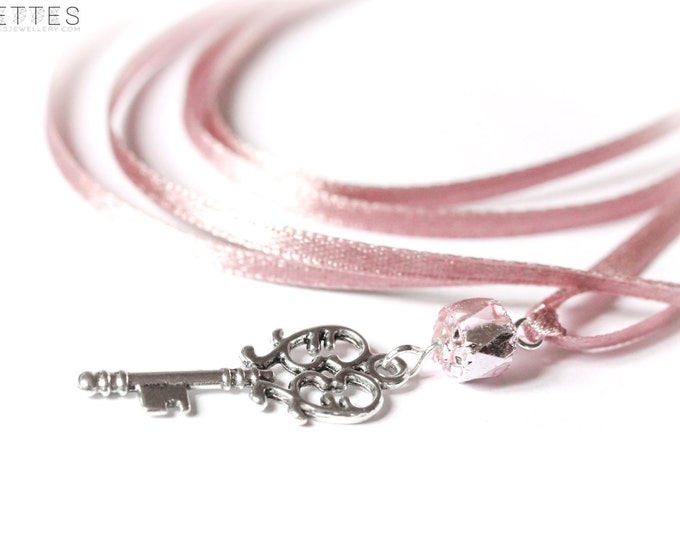 90 cm necklace/pendant with a 5 cm silver key, pink satin ribbon and pink glass bead