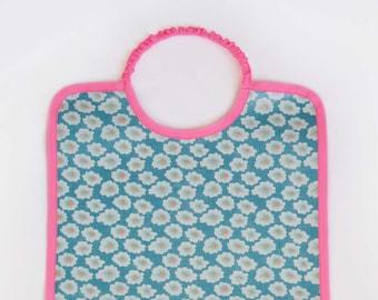 Grand bavoir en coton enduit à élastique imprimé Petit Pan bleu fleuri et biais rose fluo bébé enfant fille