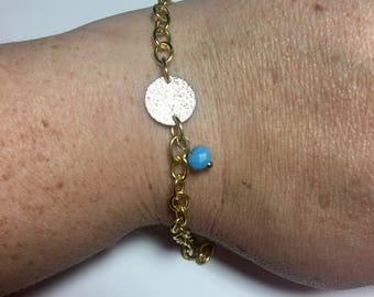 Silver tone textured disc w/gold tone chain and blue bead bracelet