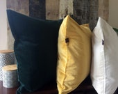 Luxury velvet pillow in deep forrest green, rich royal blue, warm golden yellow, soft off white. Classy and chic home decor