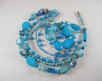 Assorted beads, different shapes, colors Blue, silver.