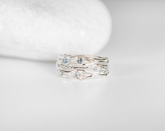 Sterling Silver Ring with Four Small Blue Topaz Gemstones on a Silver Band