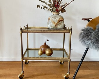 Neoclassical brass serving trolley with glass plates.