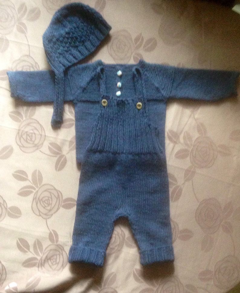 Hand knitted newborn baby coming home outfit in soft cotton acrylic mix comprises bonnet or hat jacket and dungareesoveralls