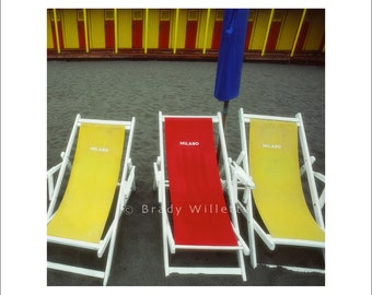 Red and yellow beach chairs on black beach with blue umbrella and yellow and red changing rooms