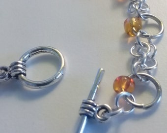 Bracelet with ring and orange stones. Toggle clasp.