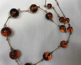 Antique Art Deco 1920s - 1930s amber orange glass, brown swirl inclusions bead necklace. Rolled gold wire chain. Length 17.5 inch or 44.5cm