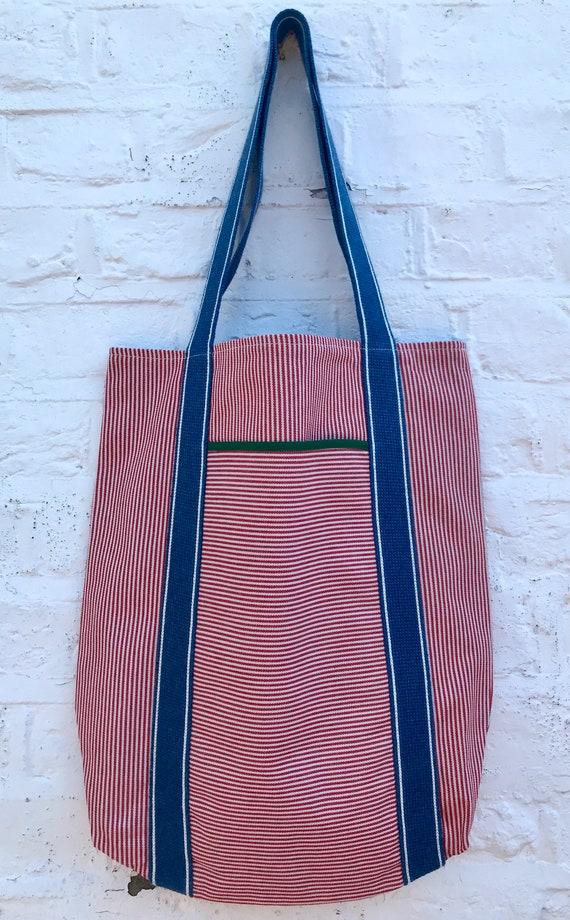 Tote bag. Red vertical striped denim bag with a deep front horizontal striped denim pocket. 100% cotton.