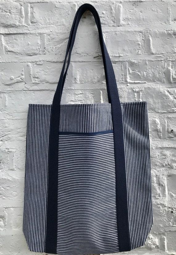 Tote bag. Navy blue vertical striped denim bag with a deep front horizontal striped denim pocket. 100% cotton.