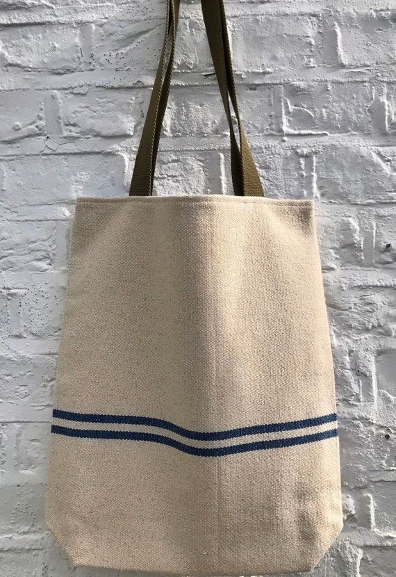 Tote bag. Heavyweight natural woven canvas with two horizontal blue stripes. Lined with a blue linen fabric.