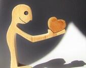 un homme offre un coeur ; sculpture bois chantourné