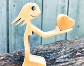 une femme offre un coeur ; sculpture bois chantourné