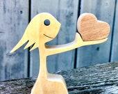 fille offre un coeur ; sculpture bois