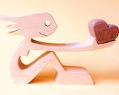 une femme assise offre un coeur ; sculpture bois
