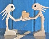 une femme offre un coeur à une femme sculpture bois chantournée