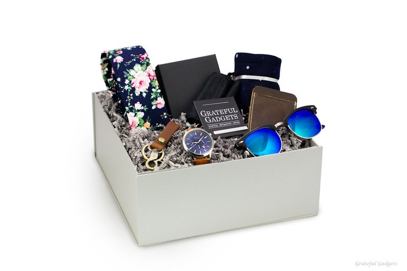 graduation gift box for him with stylish accessories like a floral tie, watch, and sunglasses