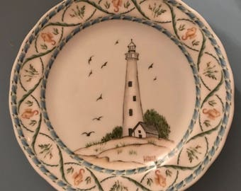 Hand painted Nautical plate featuring a light tower on a sandy beach with seagulls flying in the background.