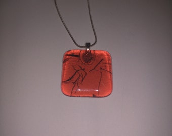 Fused glass pendant in orange, blue stringers.